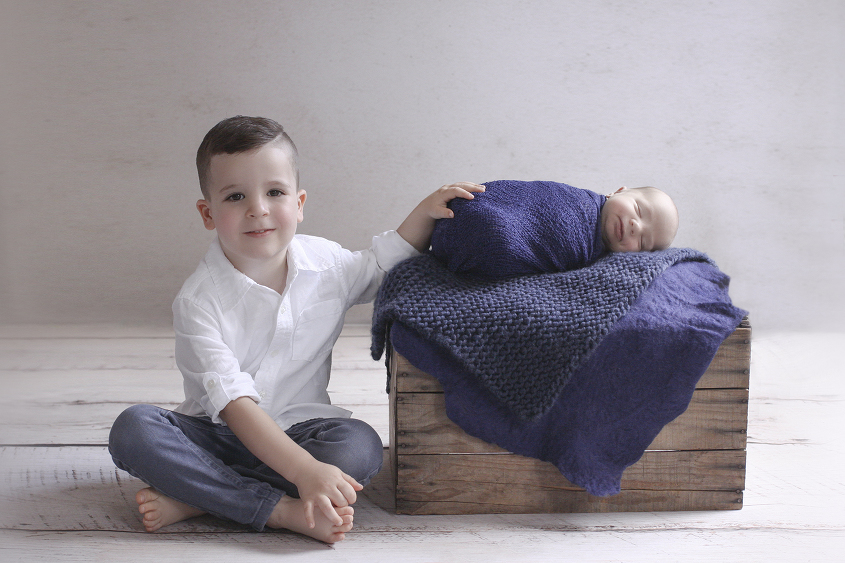 Newborn baby boy wrapped in navy blanket on wooden crate with blue knit and felt layer with sibling big brother