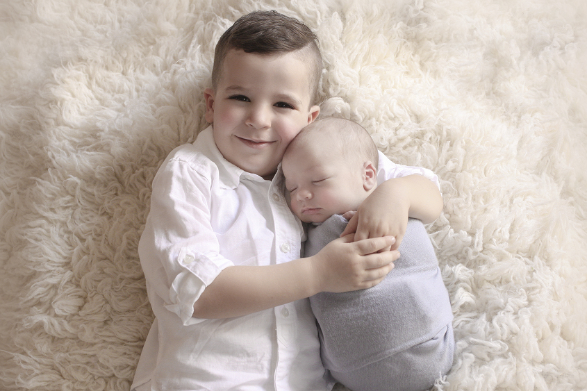 Newborn baby boy wrapped in blue wrap being held by sibling brother on cream fur
