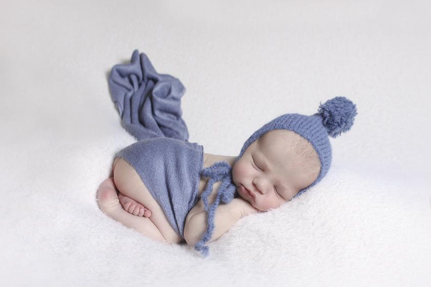 Newborn baby boy sleeping on cream blanket with blue knit bonnet and wrap