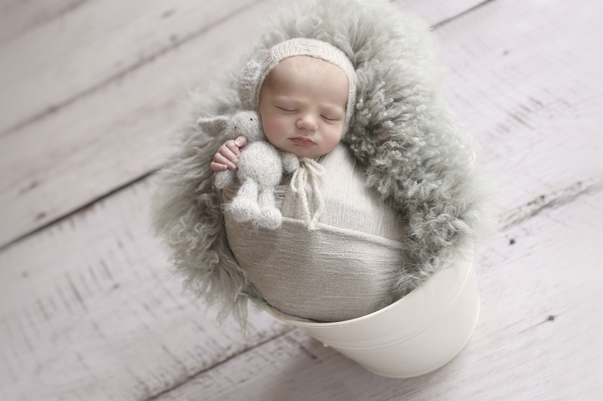 Newborn baby boy sleeping in cream tin bucket with grey curly felt and blanket and bonnet and bunny
