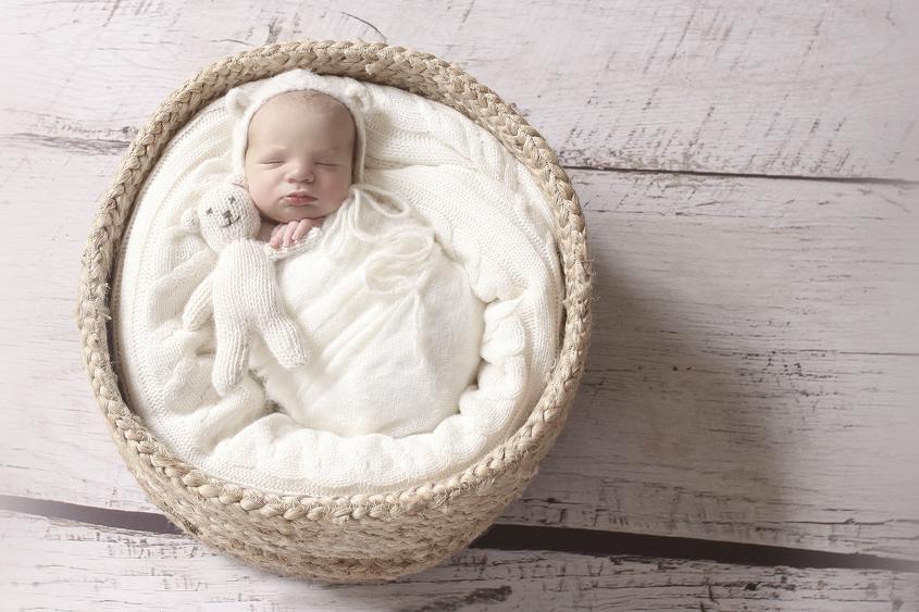 Newborn baby boy wrapped in cream wrap with cream knit bear bonnet in round cane basket on white wooden floor