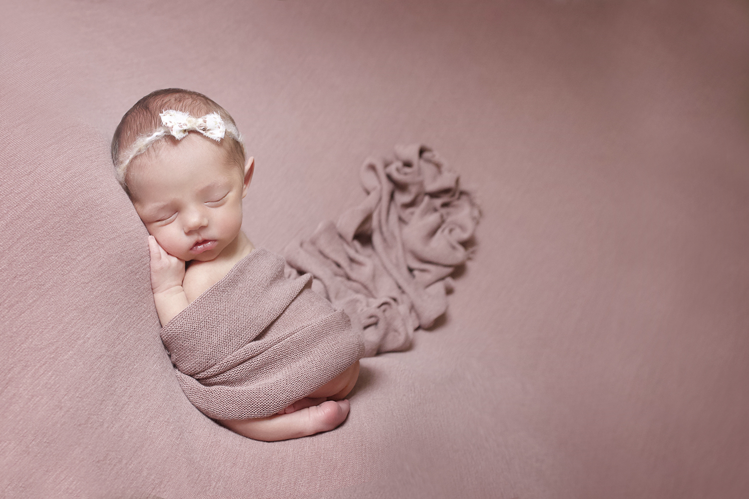 Newborn baby girl sleeping on pink blanket with pink wrap and tieback