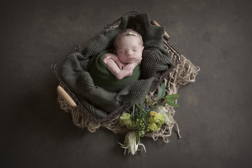 Newborn baby girl sleeping in farmers basket with olive blanket and wrap and tieback with flowers and jute layer on olive canvas drop