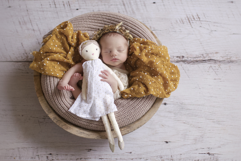 Newborn baby girl sleeping in round wooden bowl with brown blanket and mustard layer wearing brown lace romper and flower crown holding doll on white wooden floor