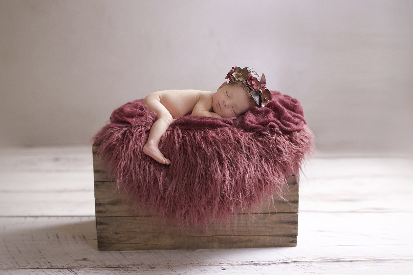 Newborn baby girl sleeping on wooden crate with burgundy curly felt layer and wrap and flower crown