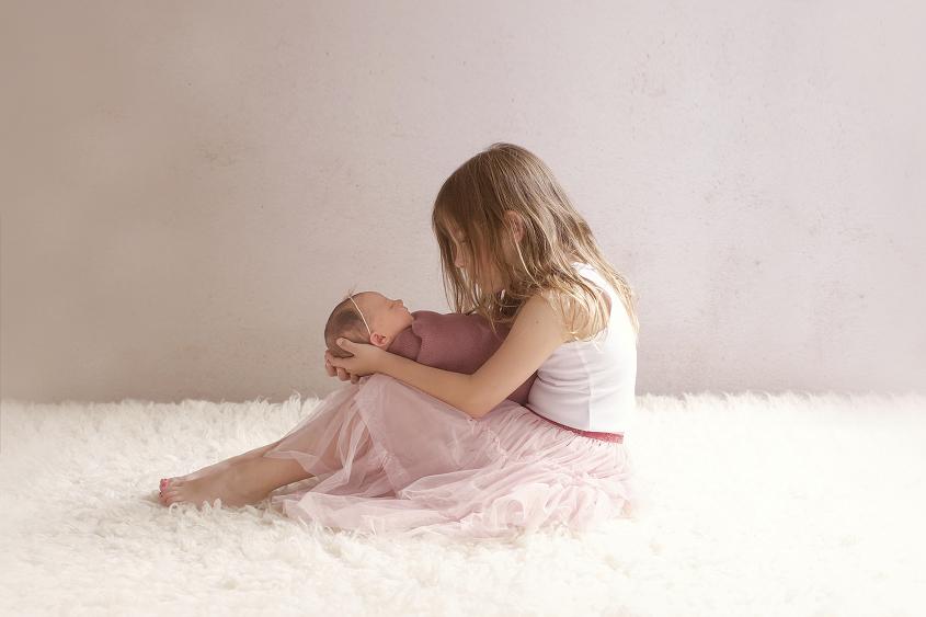 Newborn baby girl sleeping wrapped in dusty pink wrap with pink tieback being held by sibling sister on cream fur