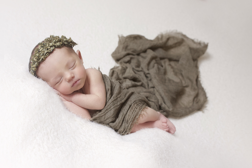 Newborn baby girl sleeping on cream blanket with olive wrap and flower crown