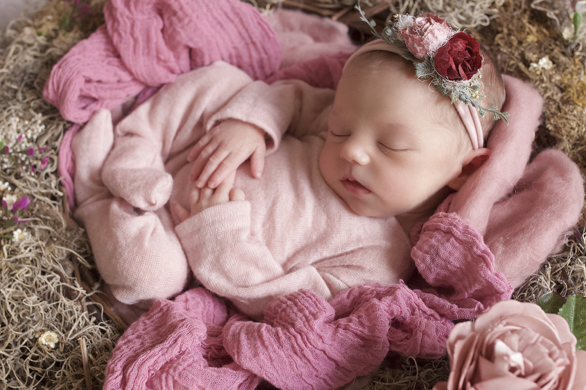 Newborn baby girl sleeping in nest with pink flowers and wraps and romper and tieback