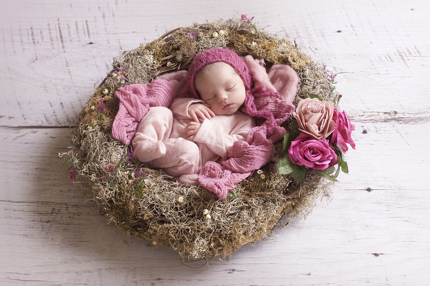 Newborn baby girl sleeping in nest with pink flowers and wraps and romper and bonnet