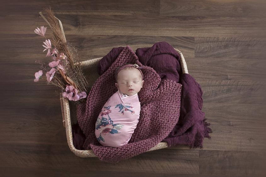Newborn baby girl sleeping in rectangle cane basket wrapped in purple floral wrap with plum knit layer and blankets and flowers on wooden floor