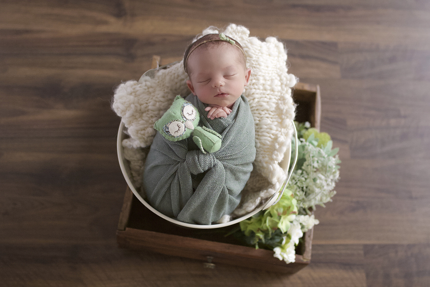 Newborn baby girl sleeping in cream bucket with mint wrap and cream knit layer in wooden drawer with flowers on wooden floor with bow tieback