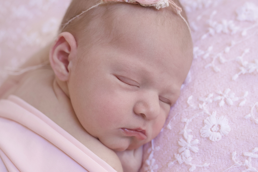 Newborn baby girl sleeping on pink lace fabric with pink wrap and tieback