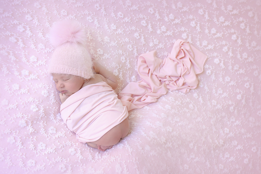 Newborn baby girl sleeping on pink lace fabric with pink wrap and pom pom beanie