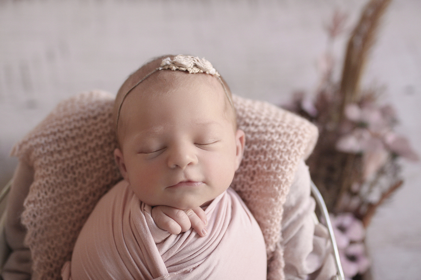 Newborn baby girl sleeping in cream bucket in wooden drawer wrapped in pink wrap with pink knit layer and blanket and flowers on white wooden floor
