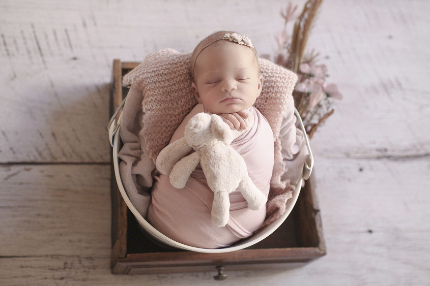 Newborn baby girl sleeping in cream bucket in wooden drawer wrapped in pink wrap with pink knit layer and blanket and flowers on white wooden floor holding soft bunny toy