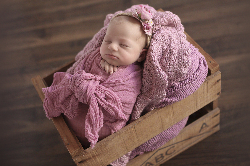 Newborn baby girl wrapped in pink wrap in wooden crate with pink knitted blanket and flower tieback on wooden floor