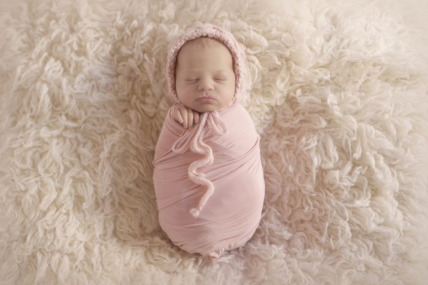 Newborn baby girl wrapped in pink wrap and knit bonnet on cream fur