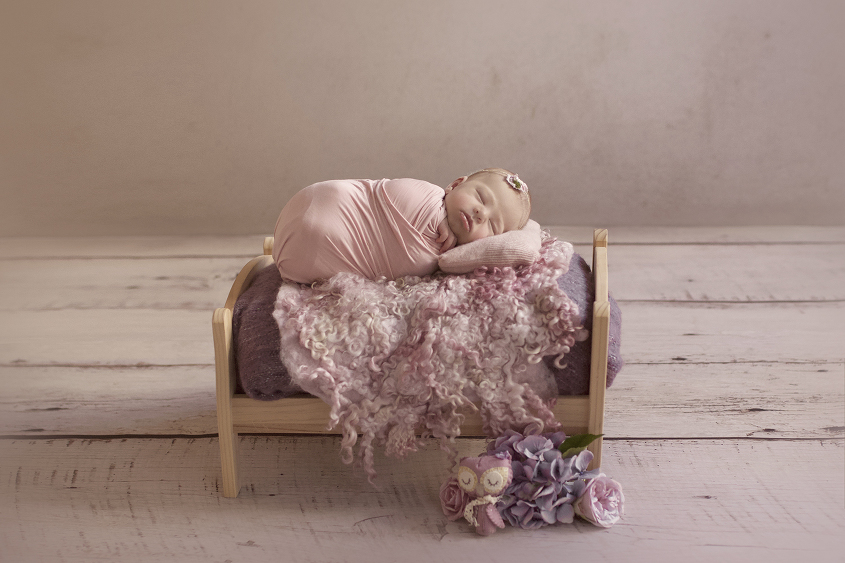 Newborn baby girl wrapped in pink wrap on wooden flower bed with purple blanket and felt layer and flowers and owl toy