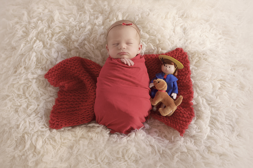 Newborn baby girl wrapped in red wrap with red knit layer with madeline toy on cream fur