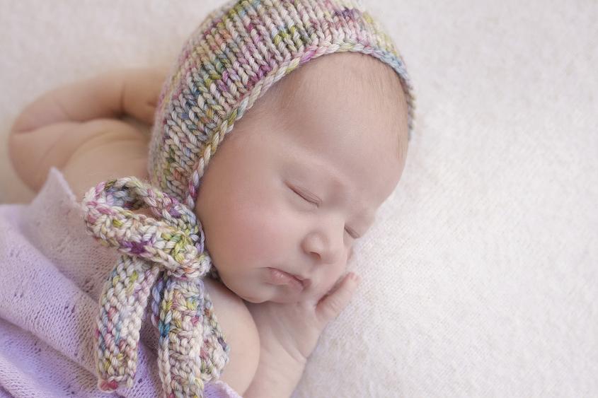 Newborn baby girl sleeping on cream blanket with purple wrap and purple knit bonnet