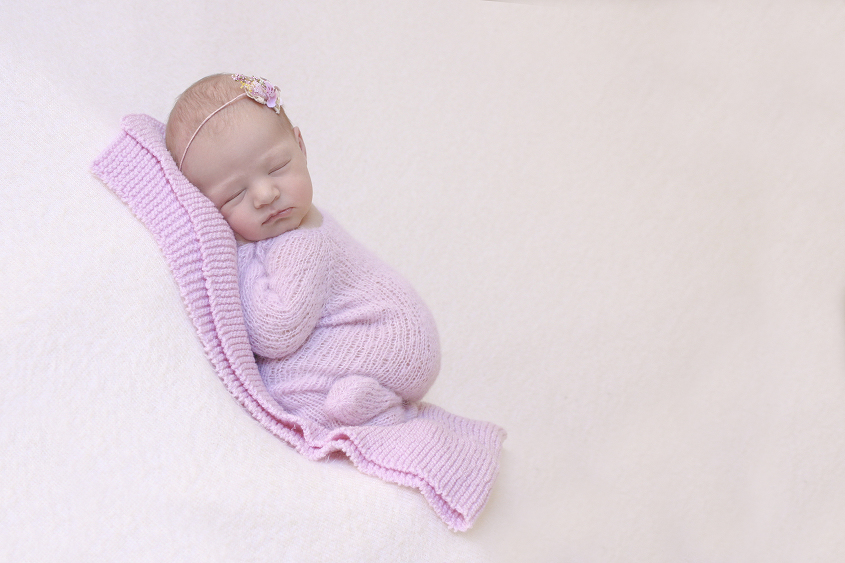 Newborn baby girl in pink knit romper on pink knit layer on cream blanket with pink tieback