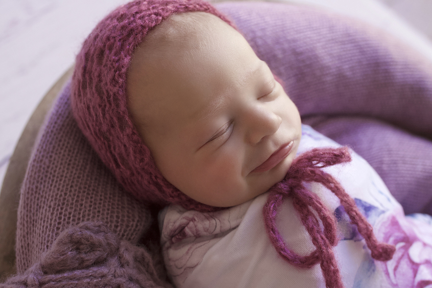 Newborn baby girl sleeping in round wooden bowl with purple blanket and purple lace wrap wrapped in white floral wrap with purple knit bonnet