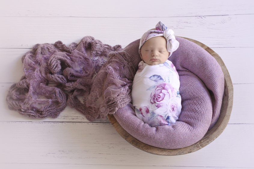 Newborn baby girl sleeping in round wooden bowl with purple blanket and purple lace wrap wrapped in white floral wrap and matching head bow