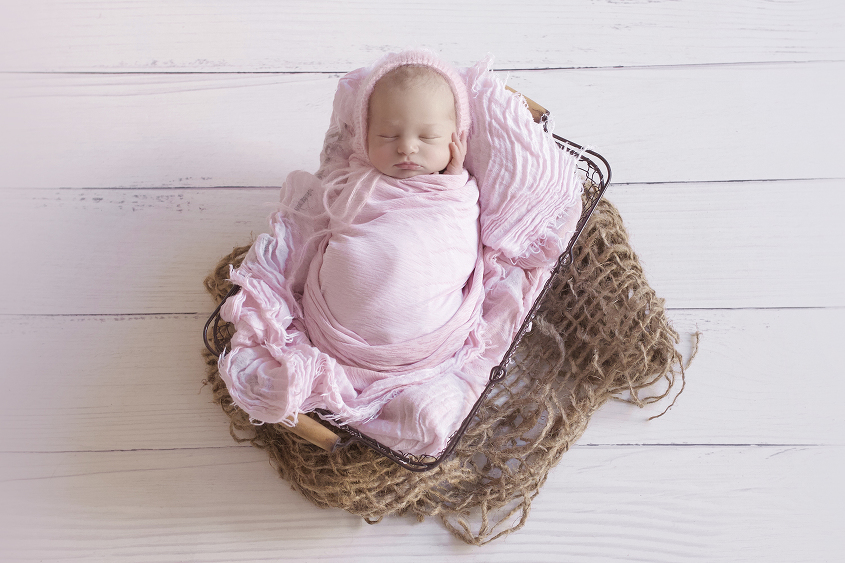 Newborn baby girl sleeping in farmers basket with pink blaket and wrap and bonnet on white wooden floor with hessian layer