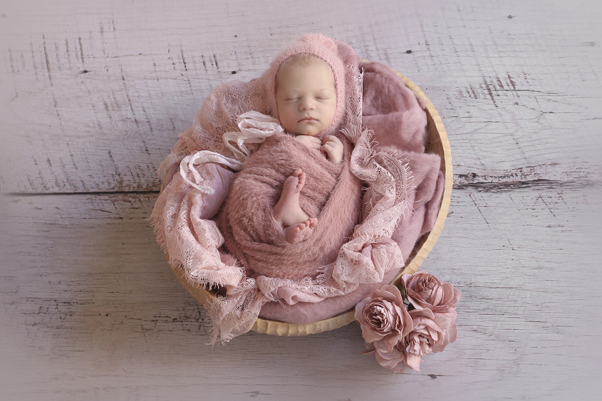 Newborn baby girl in oval wooden bowl with dusty pink wraps and layers and bonnet and flowers on white wooden floor