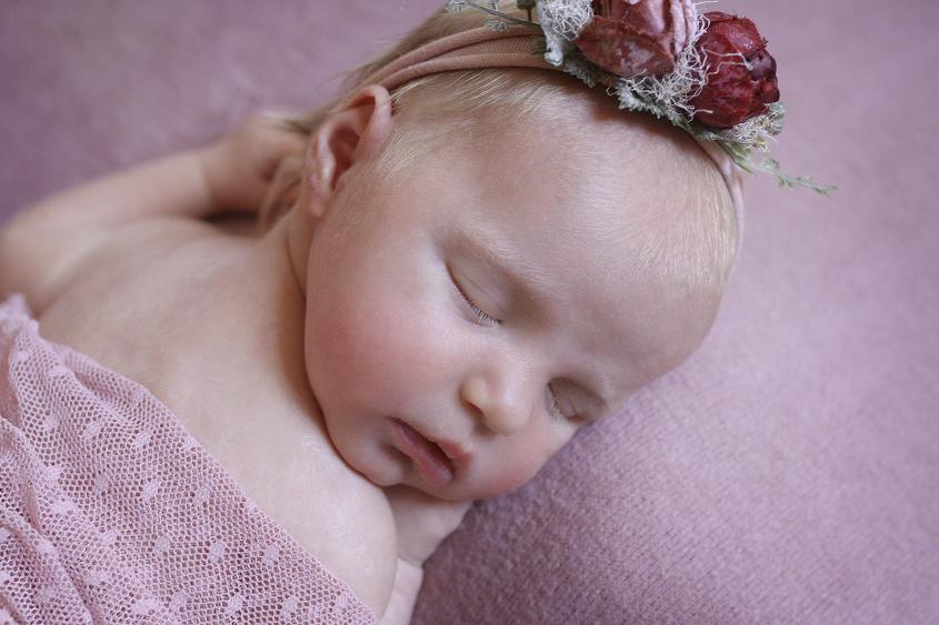 Sleeping newborn girl on pink blanket with pink wrap and flower headband