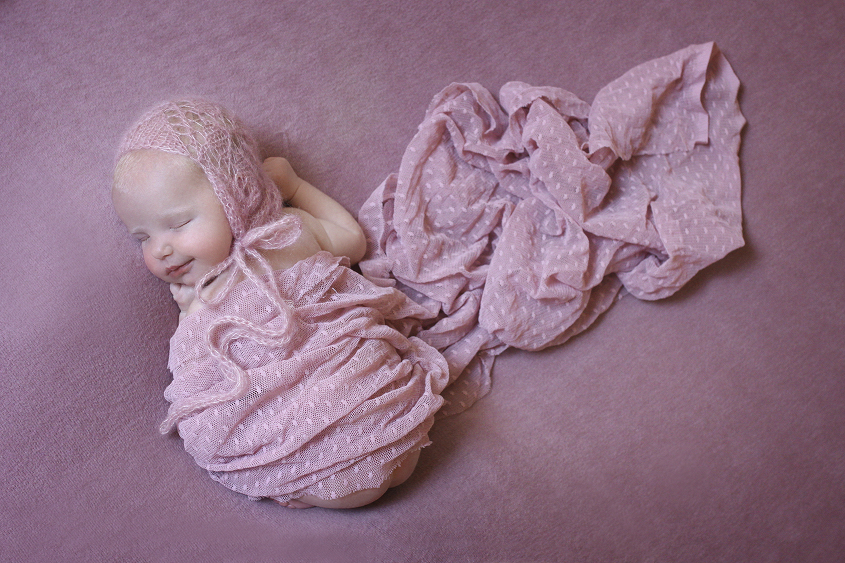 Sleeping newborn girl on pink blanket with pink wrap and knit bonnet