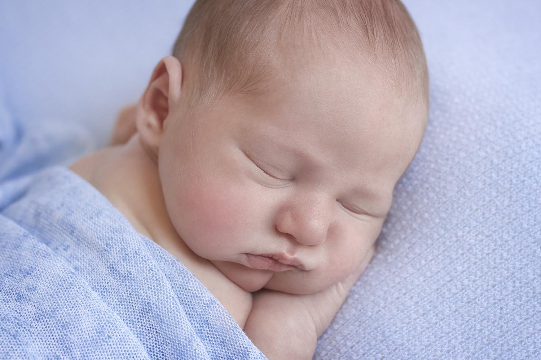 Newborn baby boy sleeping on blue blanket with blue wrap