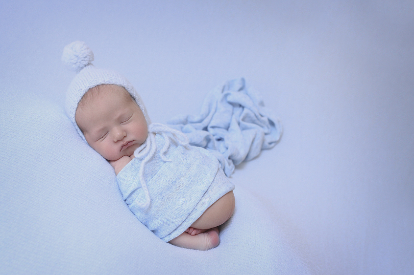 Newborn baby boy sleeping on blue blanket with blue wrap and blue knit bonnet
