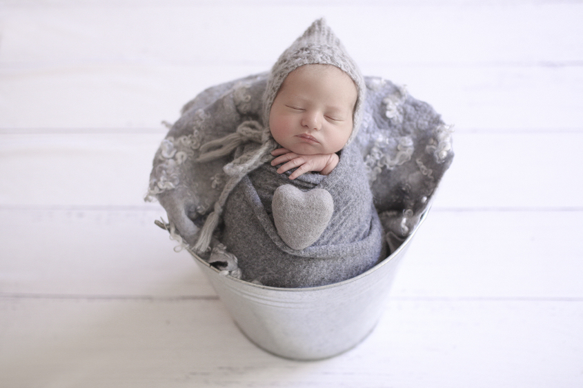 Newborn baby boy sleeping in tin bucket with grey wrap and knit bonnet and felt heart and curly felt layer