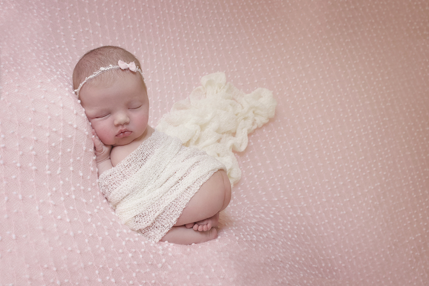 Newborn baby girl sleeping on pink spotted blanket with cream blanket and bow tieback