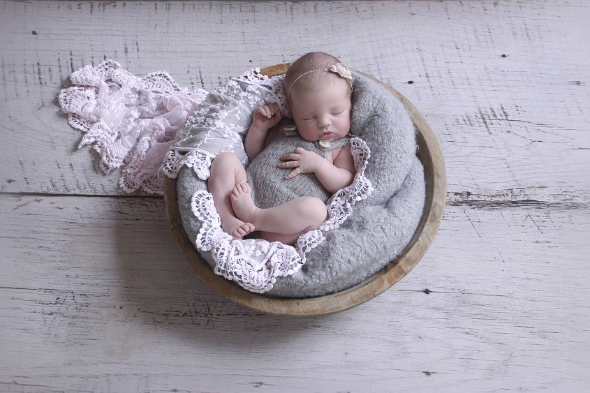 Newborn baby girl sleeping in round wooden bowl wearing grey knit romper with pink lace wrap, flower tieback and grey blanket on white wooden floor