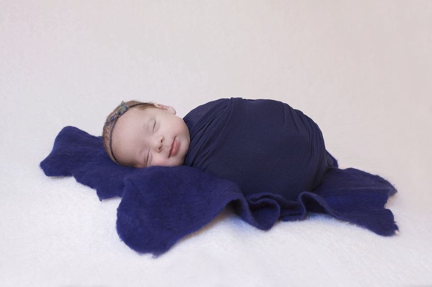 Newborn baby girl wrapped in blue blanket sleeping on cream blanket with blue bow tieback and blue felt layer