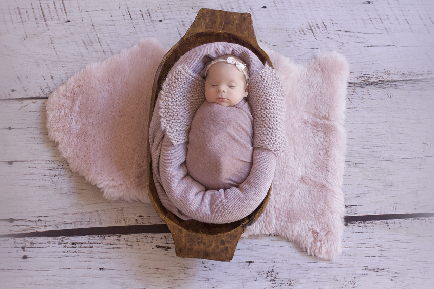 Newborn baby girl sleeping in wooden trencher with purple blanket and wrap and pink sheepskin on white wooden floor