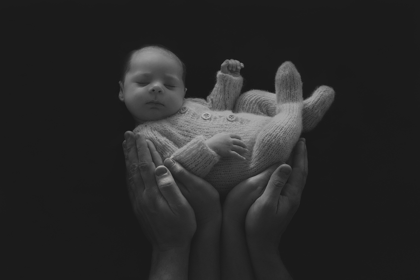 Newborn baby girl wearing knit romper being held in parents hands in black and white