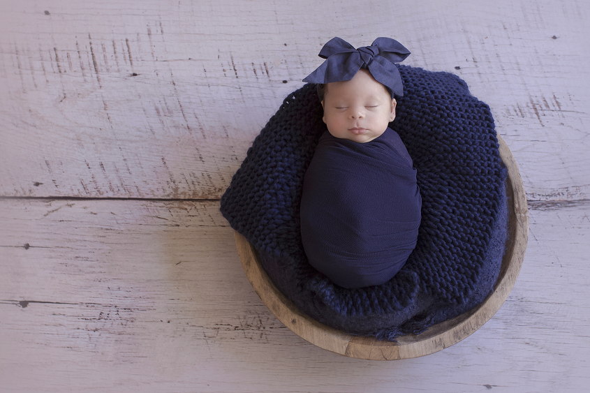 Newborn baby girl sleeping in wooden bowl with navy wrap and navy knit layer and navy bow on white wooden floor