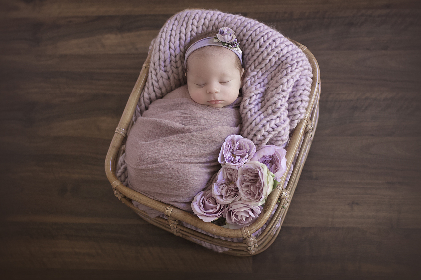 Newborn baby girl sleeping in cane basket wrapped in purple wrap with purple knit layer and flowers on wooden floor