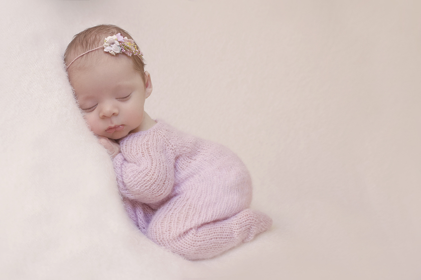 Newborn baby girl sleeping on cream blanket wearing pink knit romper and flower tieback