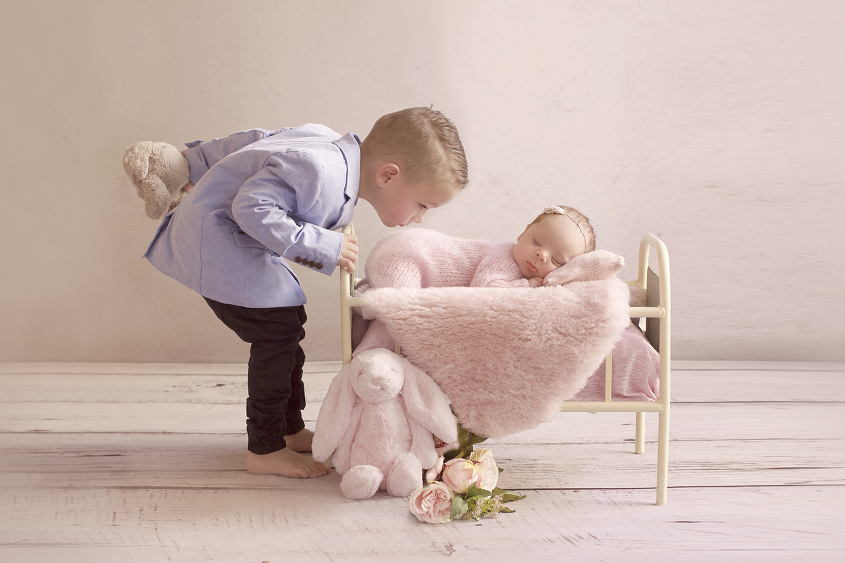 Newborn baby girl sleeping in cream iron bed wearing pink knit romper and tieback with pink sheepskin layer and flowers and bunny toy being kissed by sibling brother wearing blue jacket and jeans holding toy bunny