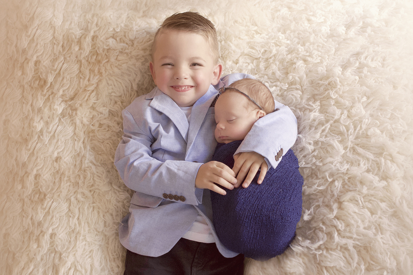 Newborn baby girl sleeping wrapped in navy wrap with bow tieback being held by smiling sibling big brother wearing blue jacket white tshirt and jeans laying on cream fur