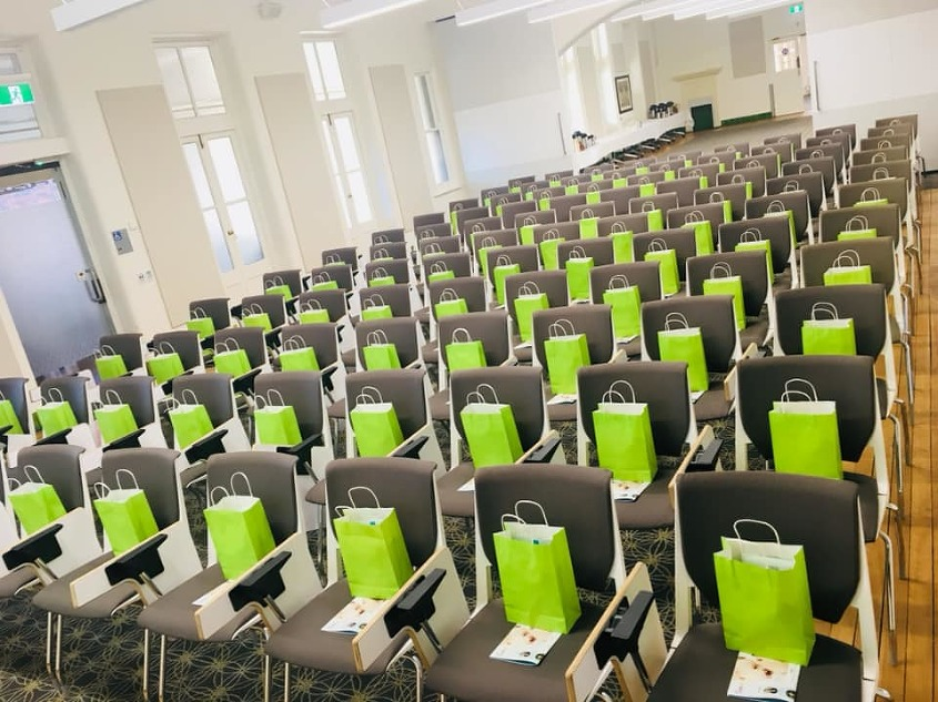 Rows of seats with green gift bags on each seat in a room