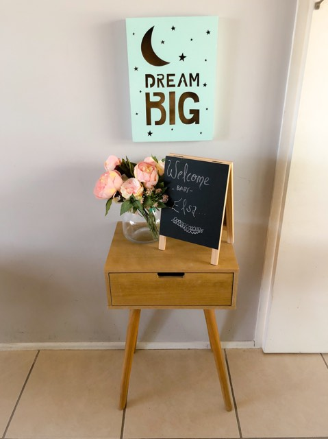 Small table with glass vase of pink flowers and black board with the words welcome baby elsa and green sign on the wall that says Dream Big