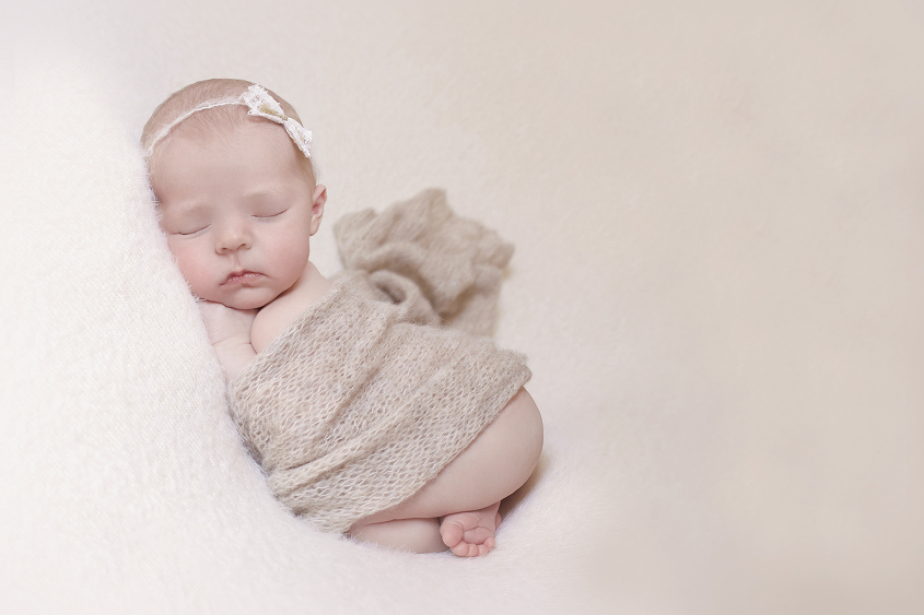Newborn baby girl sleeping on cream blanket with tan knit wrap and lace bow tieback