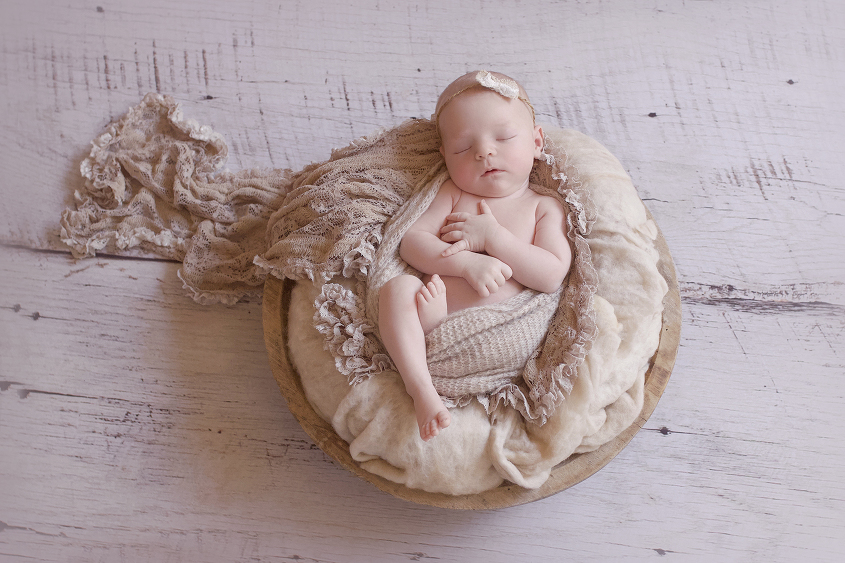 Newborn baby girl sleeping in round wooden bowl with cream felt and brown lace wrap wrapped in tan knit wrap with lace bow tieback on wooden floor