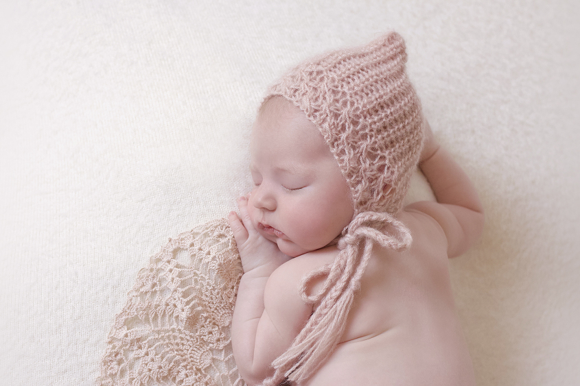 Newborn baby girl sleeping on cream blanket with pink lace doily and pink knit beanie
