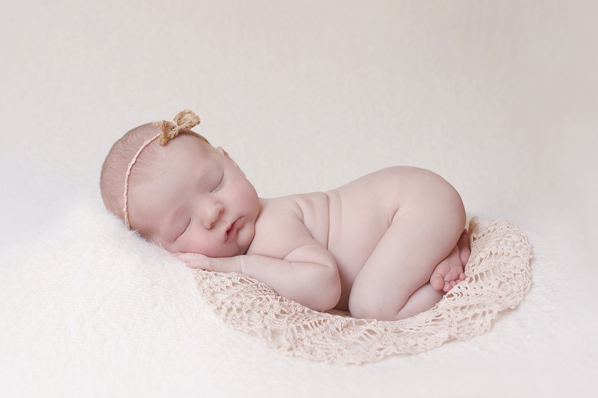 Newborn baby girl sleeping on cream blanket with pink lace doily and pink bow tieback
